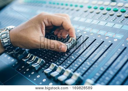 close up Hand adjusting audio mixer, Mix frequency mixer, supervising sound quality and an equalizer on the audio mixer.