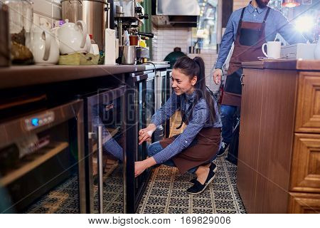 Girl barista bartender waiter in uniform making coffee at the bar.