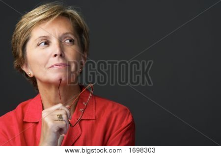 Mid adult woman holding glasses and looking sidewards poster