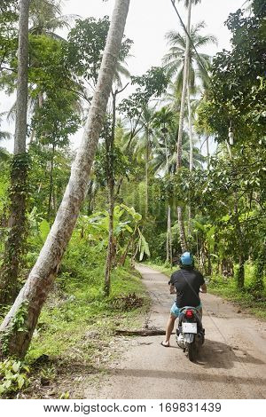 Rear view of young man riding scooter on an unpaved road; Koh Pha Ngan; Thailand