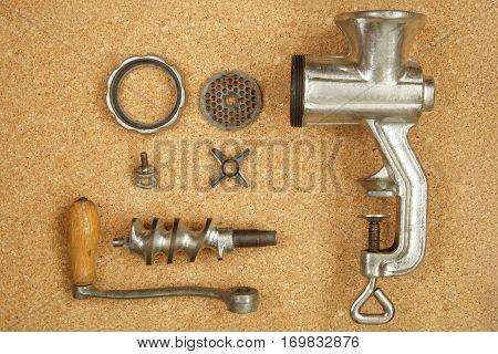 Old manual meat grinder disassembled on the cork background