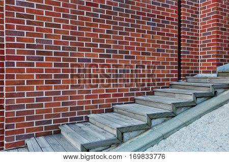 Wooden staircase with brick wall background. The ladder to success