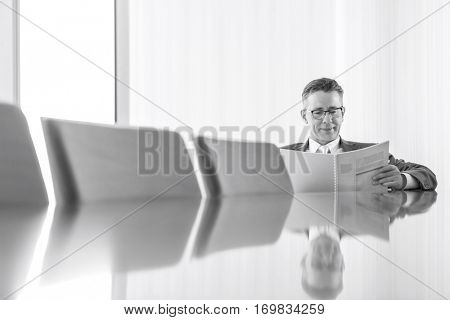Middle-aged businessman reading book at conference table