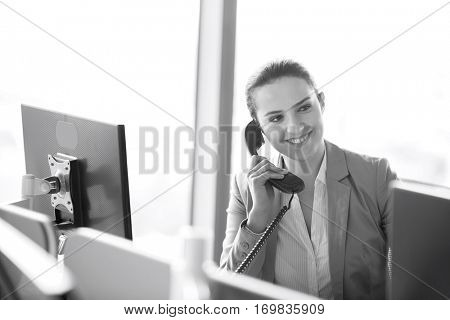 Young businesswoman talking on telephone in office