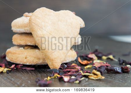A stack of biscuits and scattered tea leaves on the table
