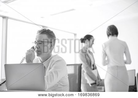 Businessman talking on telephone with colleagues in background at office