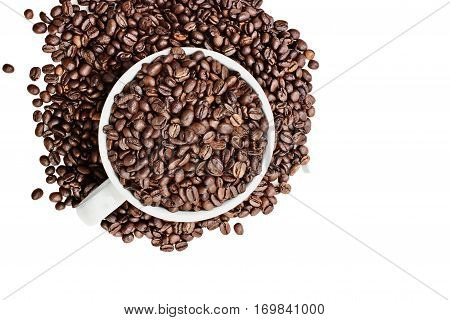 Top view of coffee beans overflowing from a ceramic cup isolated over a white background with room for copy space. Flat lay style.