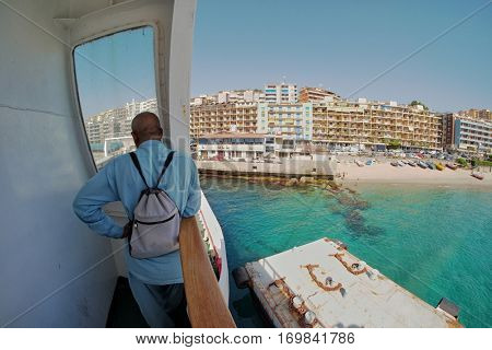 BARI, ITALY - JULY 13, 2016: thoughtful man with small backpack standing on ferry looking at Messina city skyline