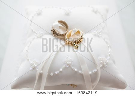 Wedding rings on white pillow with lace and beads. Unusual engagement rings on decorative hand made pillow. Golden female male ring with pendants. Jewelry accessory for wedding day. Symbol of love