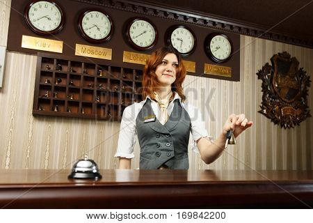 Hotel reception. Female receptionist gives key to a guest. Modern hotel counter desk with bell. Travel, hospitality, booking concept.