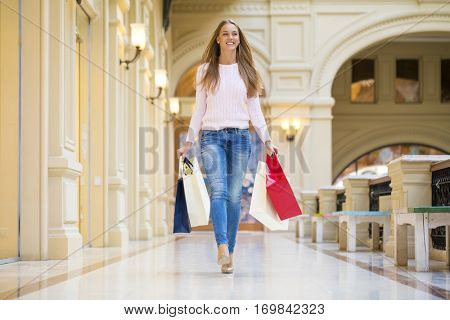 Young beautiful blonde woman with some shopping bags walking in the mall