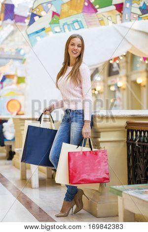 Happy Young beautiful blonde woman holding shopping bags in the mall