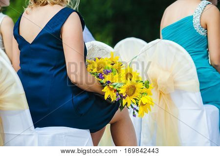 Woman guest at the wedding sitting on chair with big yellow sunflower bouquet. Bridesmaid with flowers. Delicate beautiful flowers accessory elegant bunch of fresh flowers with leaves in lady's hands