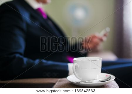 Cup of coffee on a saucer with a tea spoon focused on the background of handsome man with mobile phone. Young businessman has a coffee break. Handsome bridegroom in morning drinks hot beverage