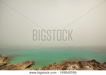 Sunset at seaside. Shore with stones and blue sky on background in heavy fog, Seascape skyline with clouds