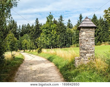 Stone shrine or chapel next to the beaten track, relaxed walk, summer countryside landscape, bottom copy space
