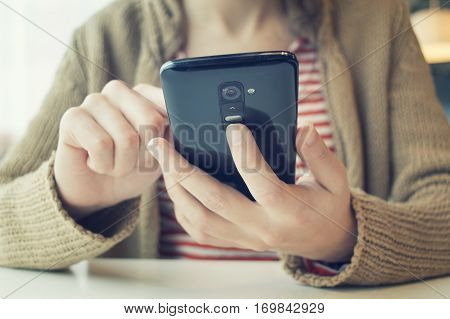 Young Woman Using Smart Phone At Cafe