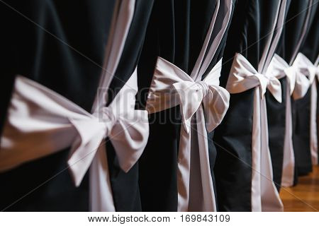 Decorated chairs with black fabric and big pink satin bows. Silk bow tied on back of chair in party at restaurant. Dark cloth cover chairs standing in a row