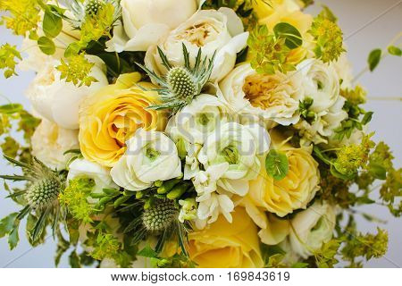 Wedding bouquet of delicate peonies and elegant roses decorated with green gipsy flowers and eucalyptus branches. Unusual bridal bouquet with exotic plants. Bunch of fresh flowers. Accessory of bride