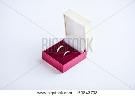 Wedding rings in box of red and white colors isolated. Golden female male ring, similar but with differences. Jewelry in square container, accessory for wedding day. Symbol of love, engagement rings