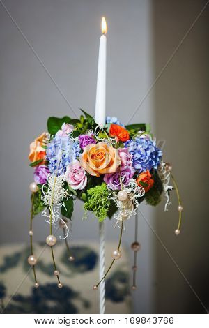 Wedding decoration element made of roses and beads. Bouquet candle holder with burning candle with colorful rose and peony flowers. Handmade candlestick for engagement ceremony decoration accessory