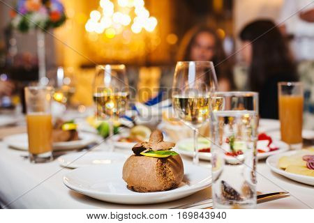 Dessert on plate at served table. Glasses with alcoholic and nonalcoholic drinks, food, guests on the background, cutlery on tablecloth