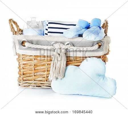 Wicker box with baby clothes and necessities on white background