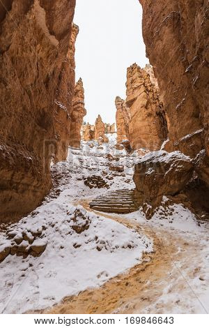 Snow covered hoodoo canyon trail at Bryce National Park in Southern Utah.