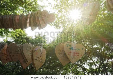 Kobe Japan 29 Aug 2015Heart shape of wood badge for a blessing in Japanese-style call EMA in Japan with the sun is shining at shrine of Nunobiki Herb Garden on Mount Rokko Kobe Japan