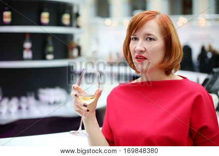 Middle age woman in red dress drinks wine during event, shallow dof