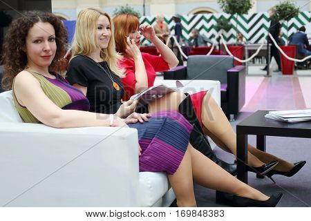 Three happy women in dresses sit on couch near table during event