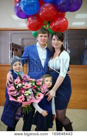 Man, woman and two little girls with flowers, balloons near cloakroom in maternity hospital