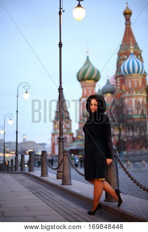 Pretty woman in mink fur coat poses near St. Basil Cathedral in Moscow