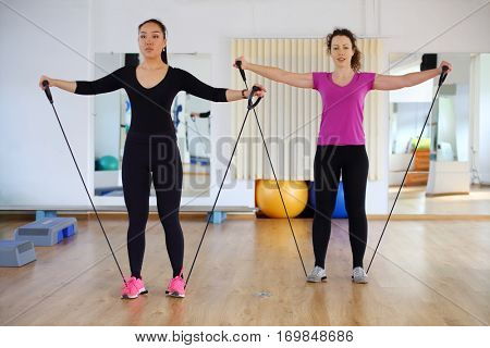 Woman and girl in sport wear trains with elastic band for fitness in modern gym