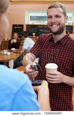 Customer Paying For Takeaway Coffee Using Contactless Terminal