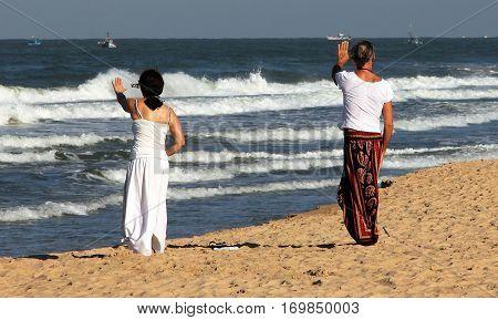 Two women practicing Qigong on the beach of Goa India