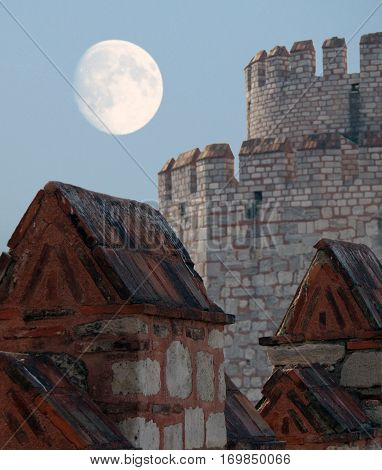 Walls of Yedikule Zindanlari (Fortress of the Seven Towers) on a background of fool moon Fatih Istanbul Turkey