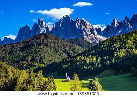 Dolomites, Tirol. Sunny warm autumn day. The famous symbol of the valley Val di Funes - church of Santa Maddalena. Rocky peaks and forested mountains surrounded by green Alpine meadows