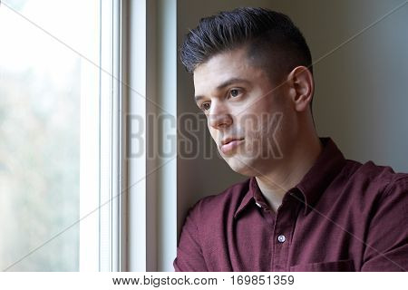 Sad Man Suffering From Depression Looking Out Of Window