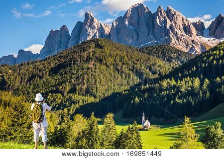 Sunny day in Dolomites, Tirol. Active elderly woman-tourist with backpack photographs the church of Santa Maddalena. Forested mountains surrounded by green Alpine meadows