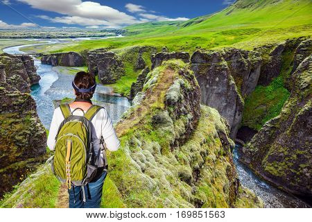 Green Tundra in summer.  The striking canyon in Iceland. The concept of active northern tourism. The elderly woman -  tourist with big backpack admiring the magnificent scenery