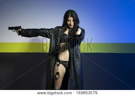 Brunette girl with handcuffs hanging in the underwear, armed and dangerous