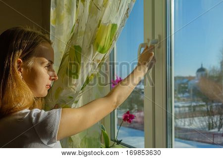 Young girl looking at snowy landscape at sunny frosty day