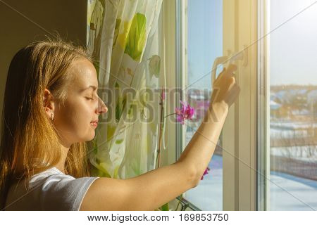 Girl is opening window and breathing fresh frosty air in snowy mountains