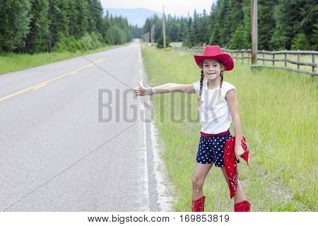 Cute little cowgirl trying to hitch hike a ride on a lonely road. Sticking out her thumb and trying to get a ride to somewhere. Homeward bound