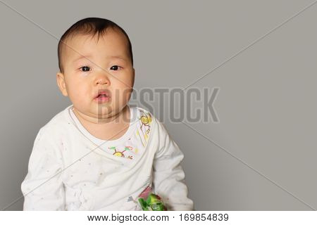 Little baby boy crying on gray background.