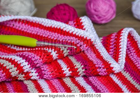 Crocheted Striped Fabric In Red Colors With Crochet Hook And Many Small Yarn Balls On The Old Wood B