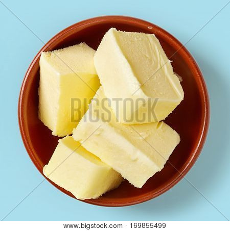 Butter In Bowl On Blue Background, From Above