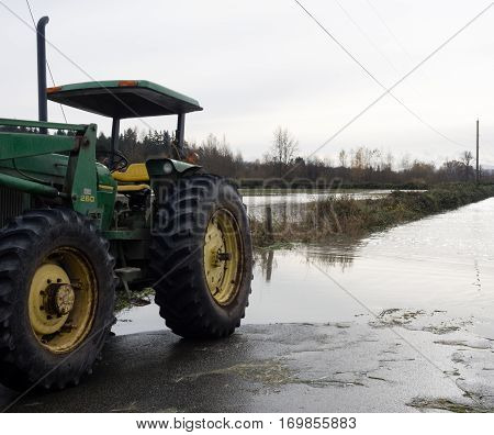 Duvall, WA, USA - November 19, 2015: Farming tractor on a flooded road during Snoqualmie river flood