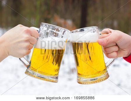 Clinking Beer Glasses On Winter Forest Background. New Year Celebration With Beer.